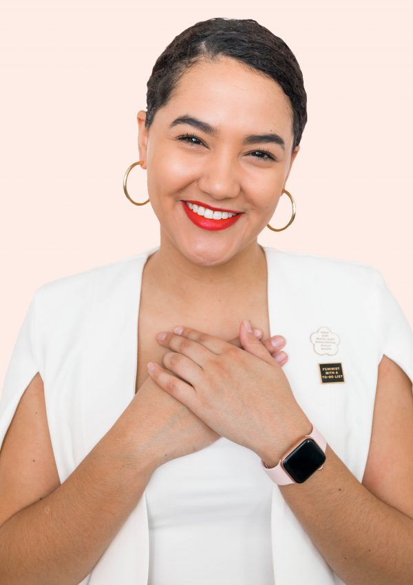girl wearing red lipstick a white blazer cape, gold hoop earrings, an apple watch, and pins