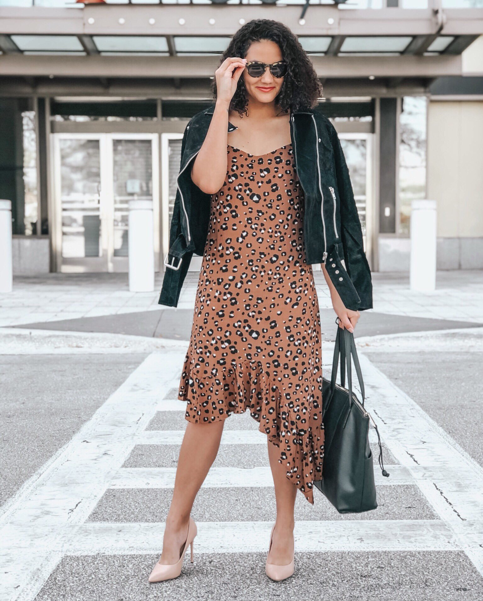 Asymmetrical Leopard print dress, Black moto jacket, black tote bag, and beige heels.
