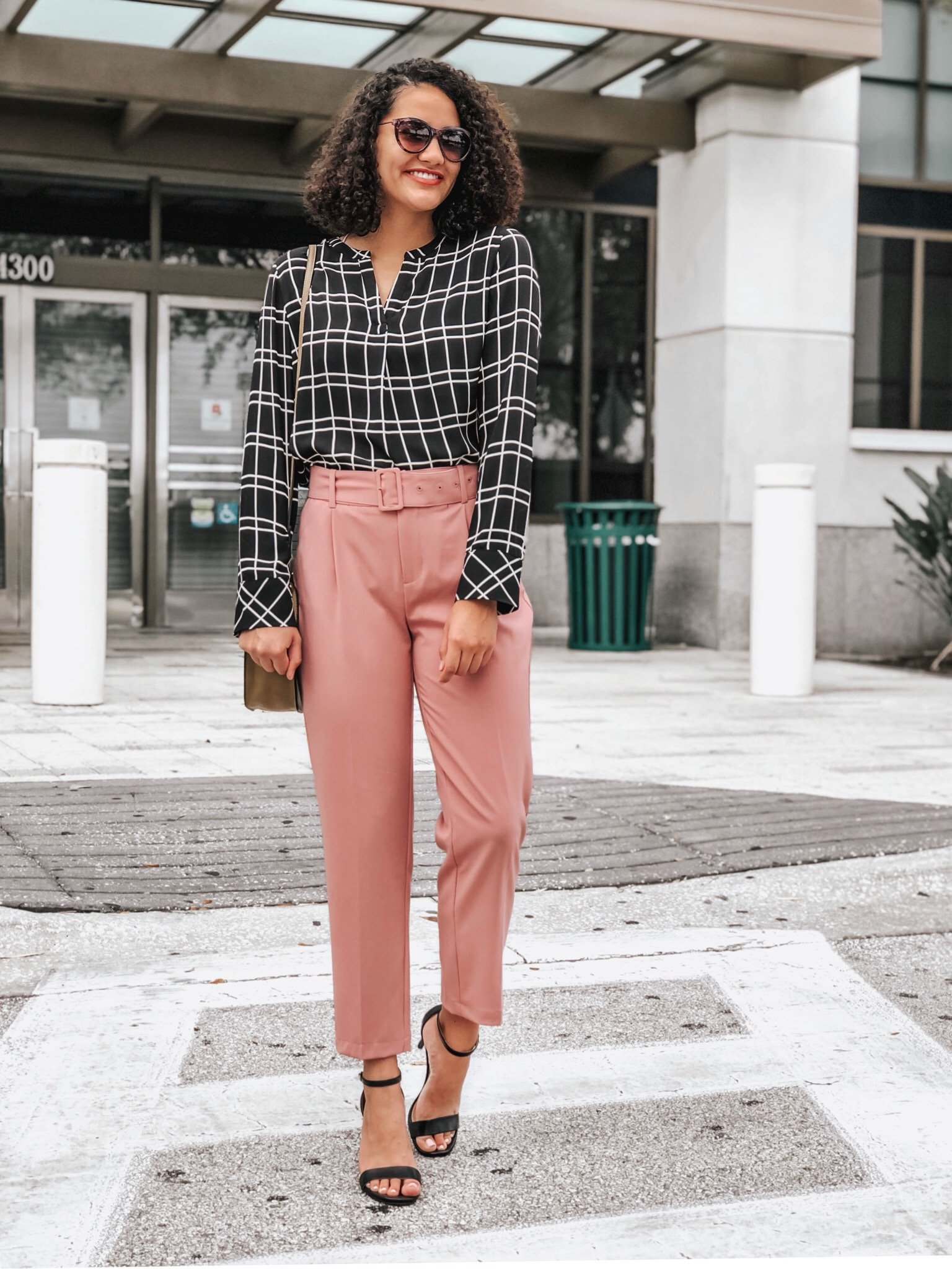 Grid print blouse, pink belted dress pants, black heels, sunglasses, and a saddle bag.