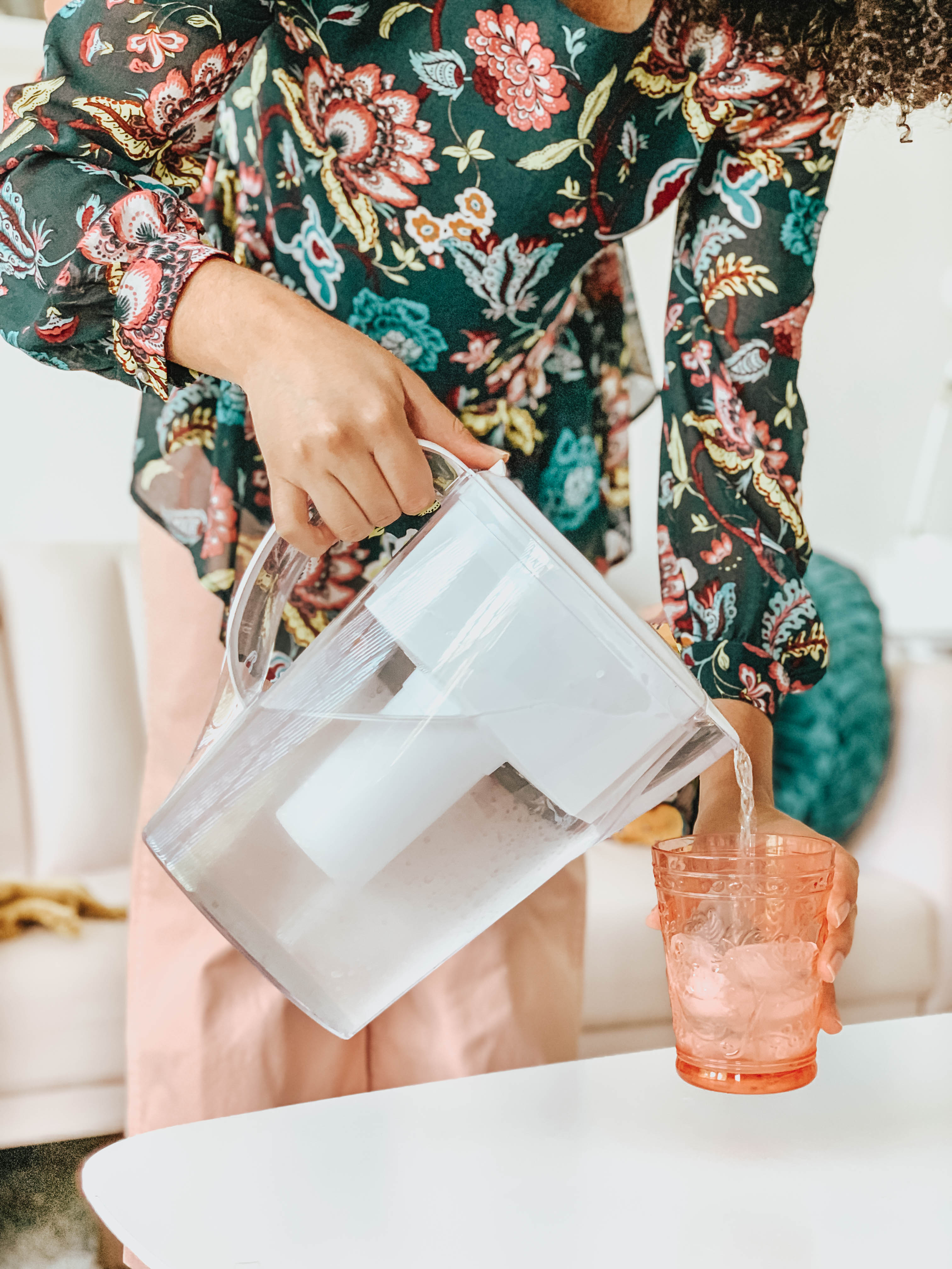 Girl pouring a cup of water with a Brita pitcher