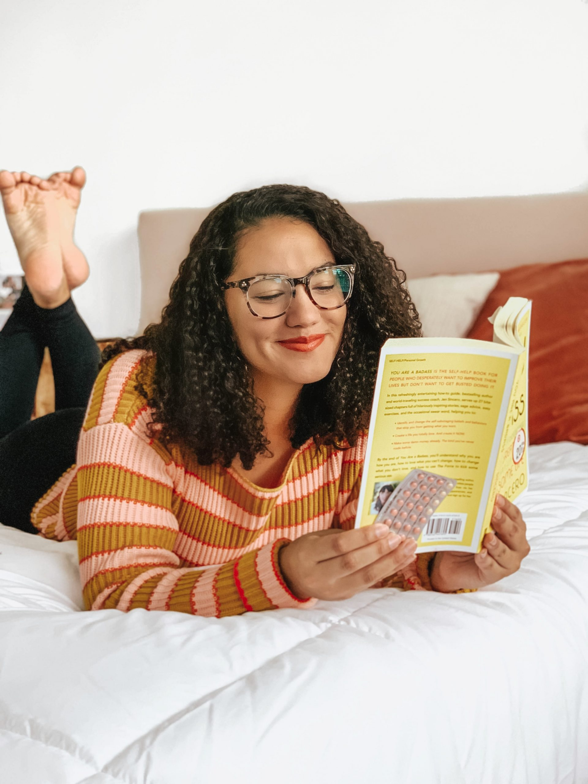 Girl Reading Book on a Bed. She is wearing glasses, a striped sweater, black leggings and is on a white comforter.