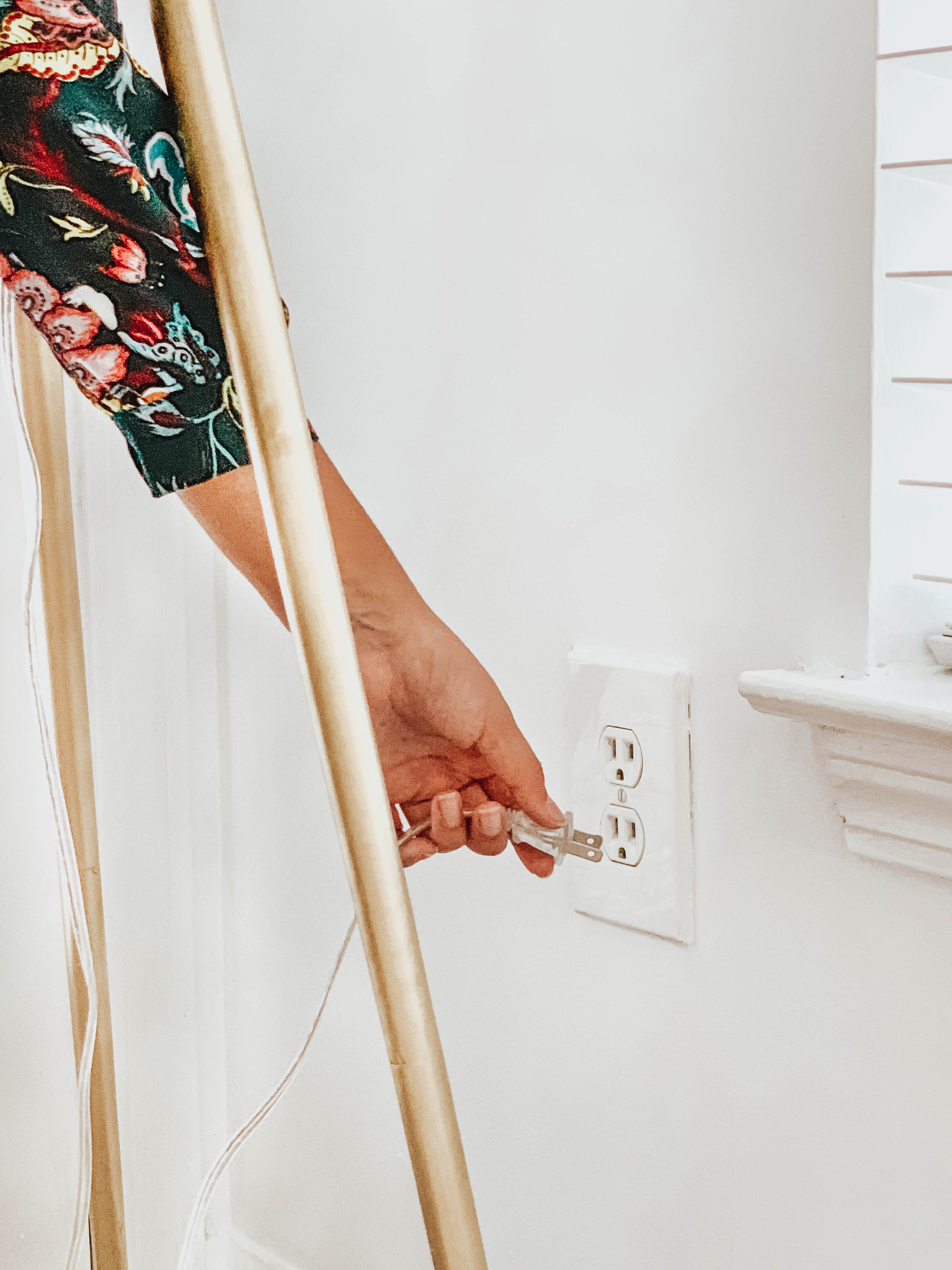 Girl Unplugging a Lamp from an Outlet