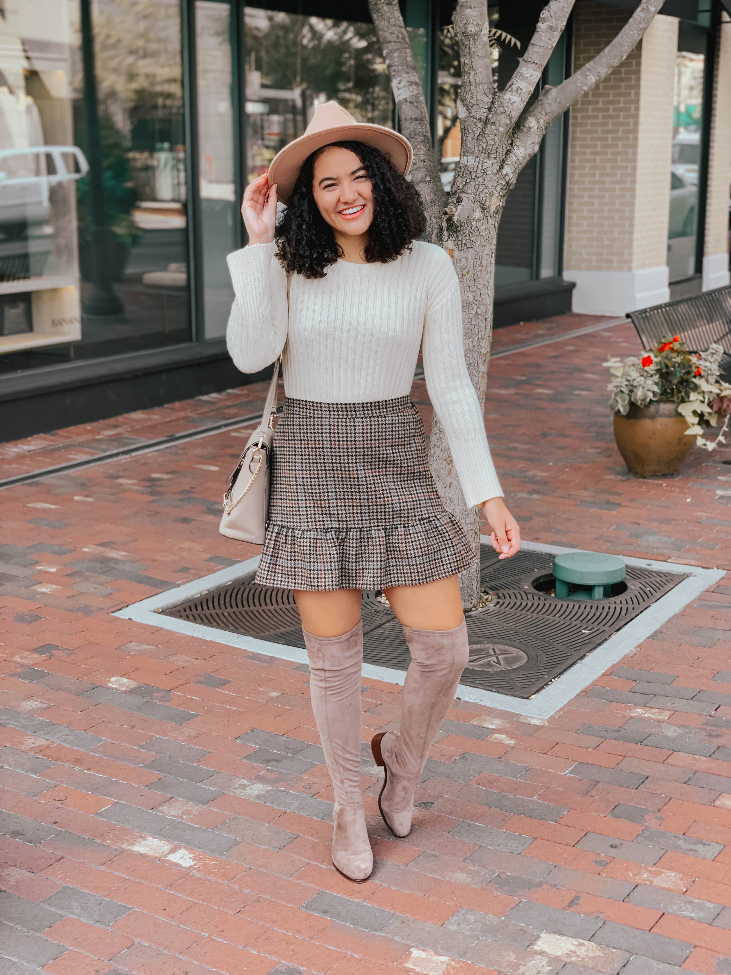 Girl with curly hair wearing a beige sweater, a plaid skirt, taupe over the knee boots, a taupe ring crossbody bag, and a tan panama hat.
