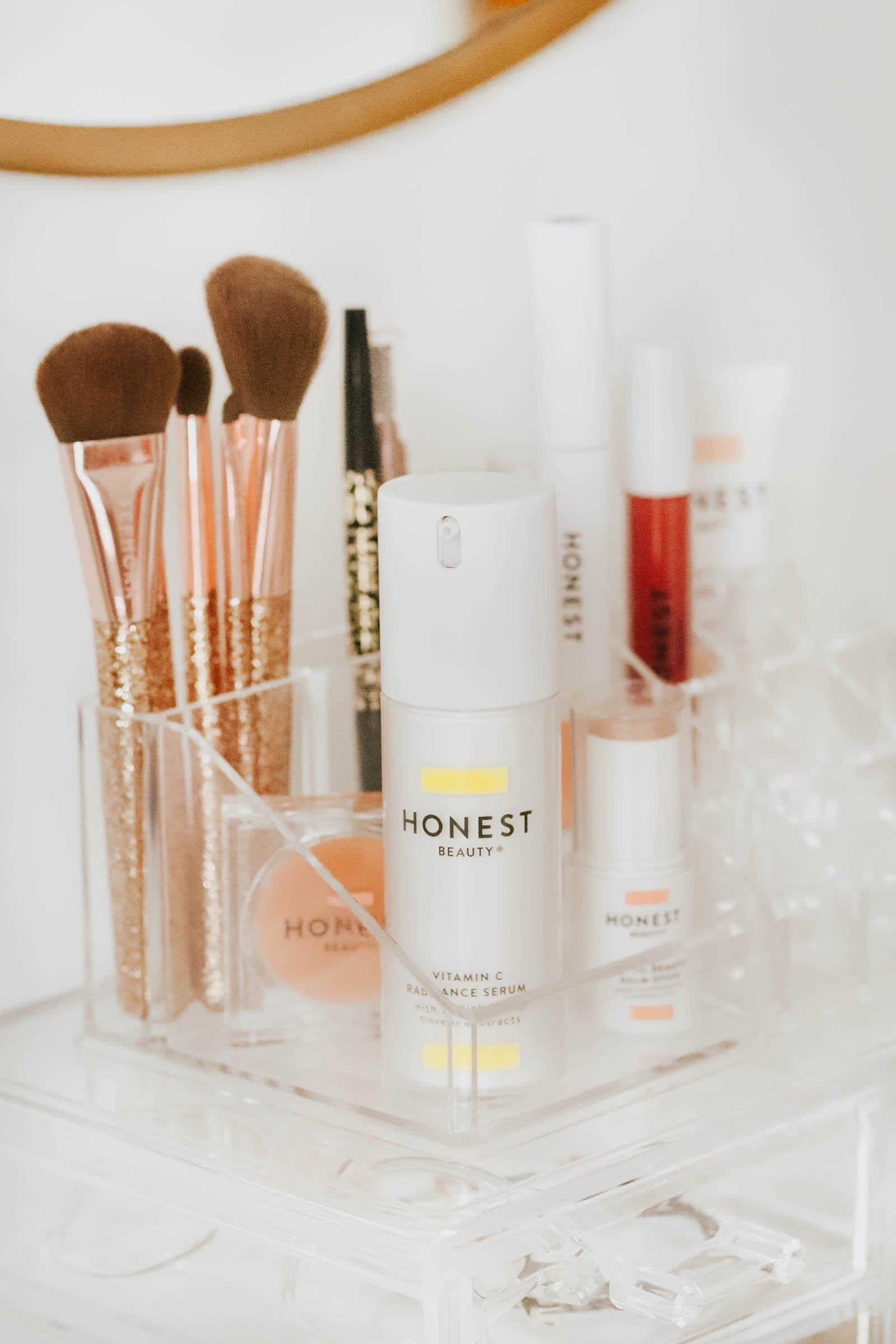Clear Makeup holder with brushes and Honest Beauty makeup products.