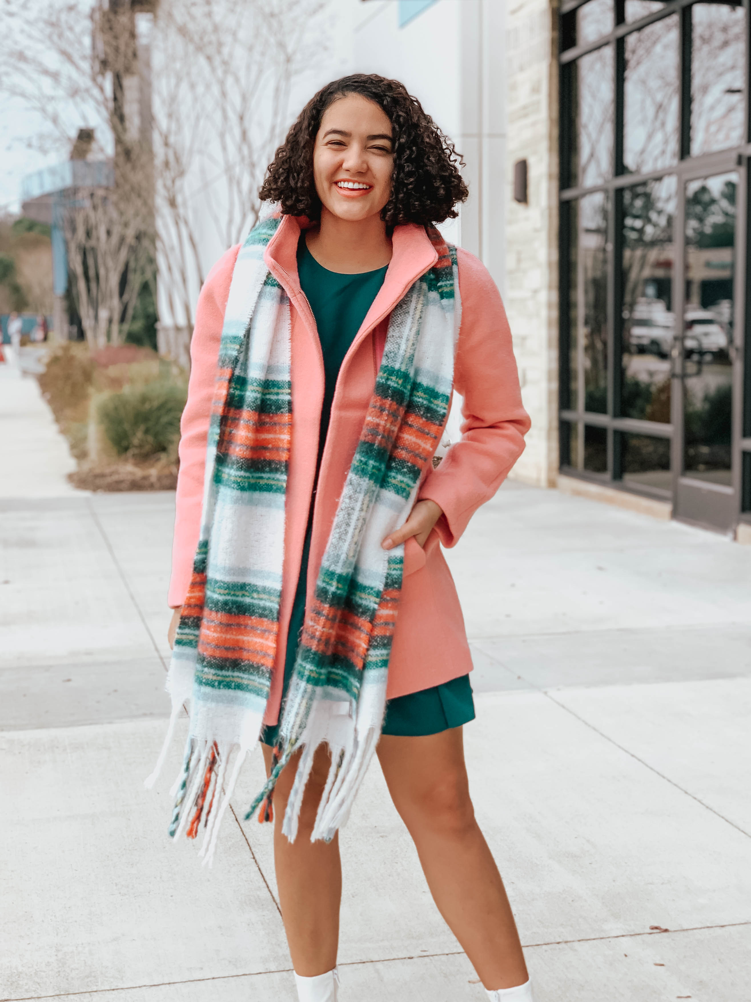 Girl with curly hair wearing a pink jacket, a plaid scarf, a teal ruffle hem dress, and white boots - Sequins and Sales