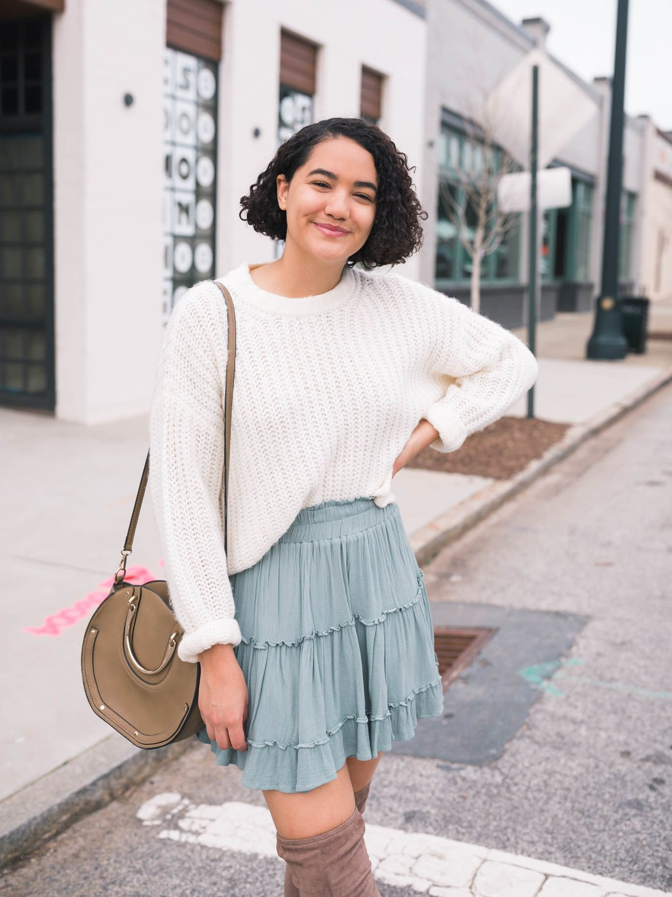cream sweater, teal tiered skirt, taupe over the knee boots, and a taupe saddle bag.