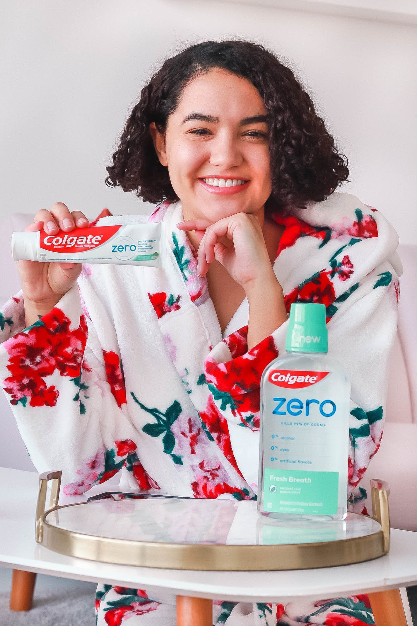 Girl with curly hair wearing a robe and holding colgate zero toothpaste and moutwash