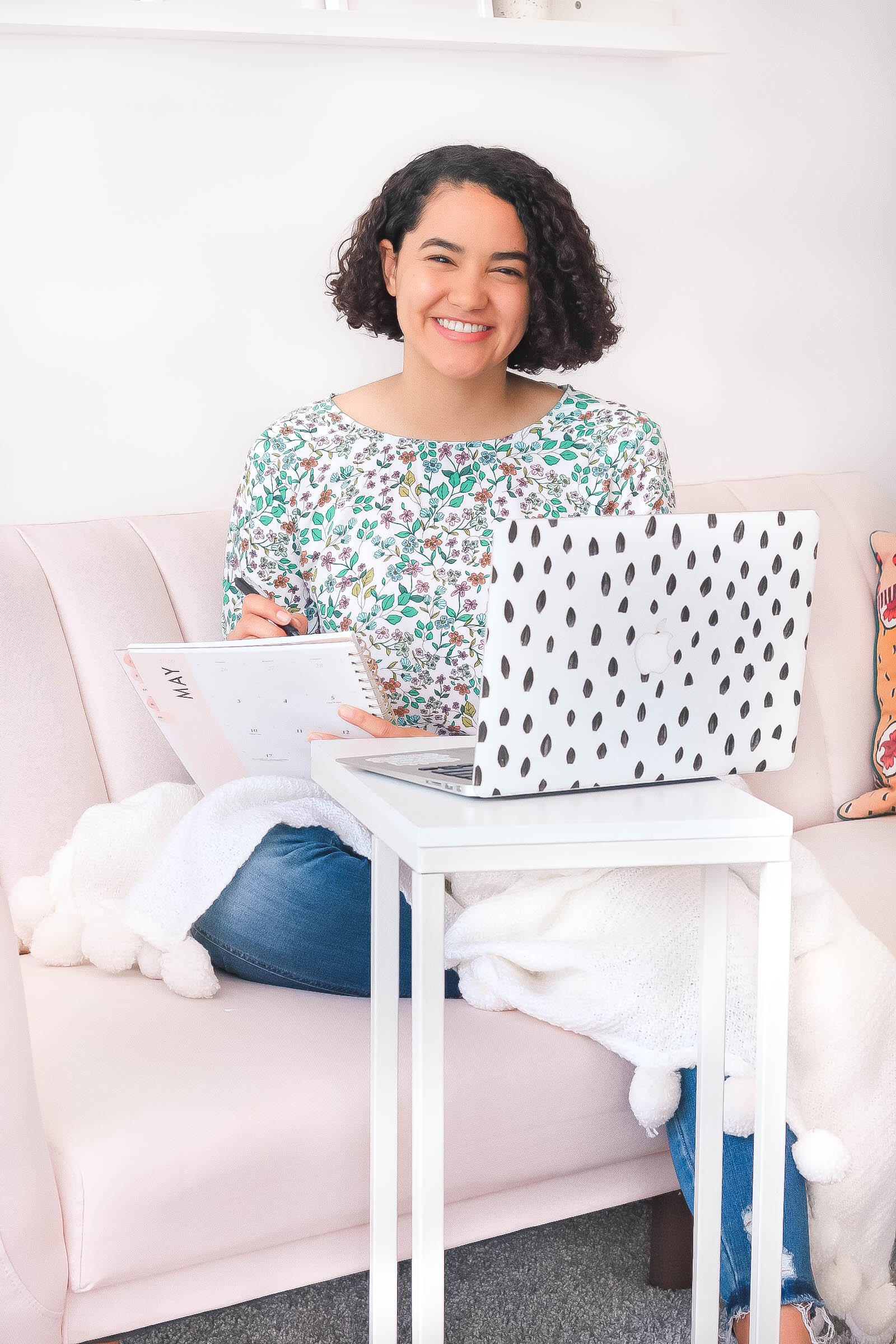 Girl with curly hair sitting on her couch working on her laptop and writing something down.