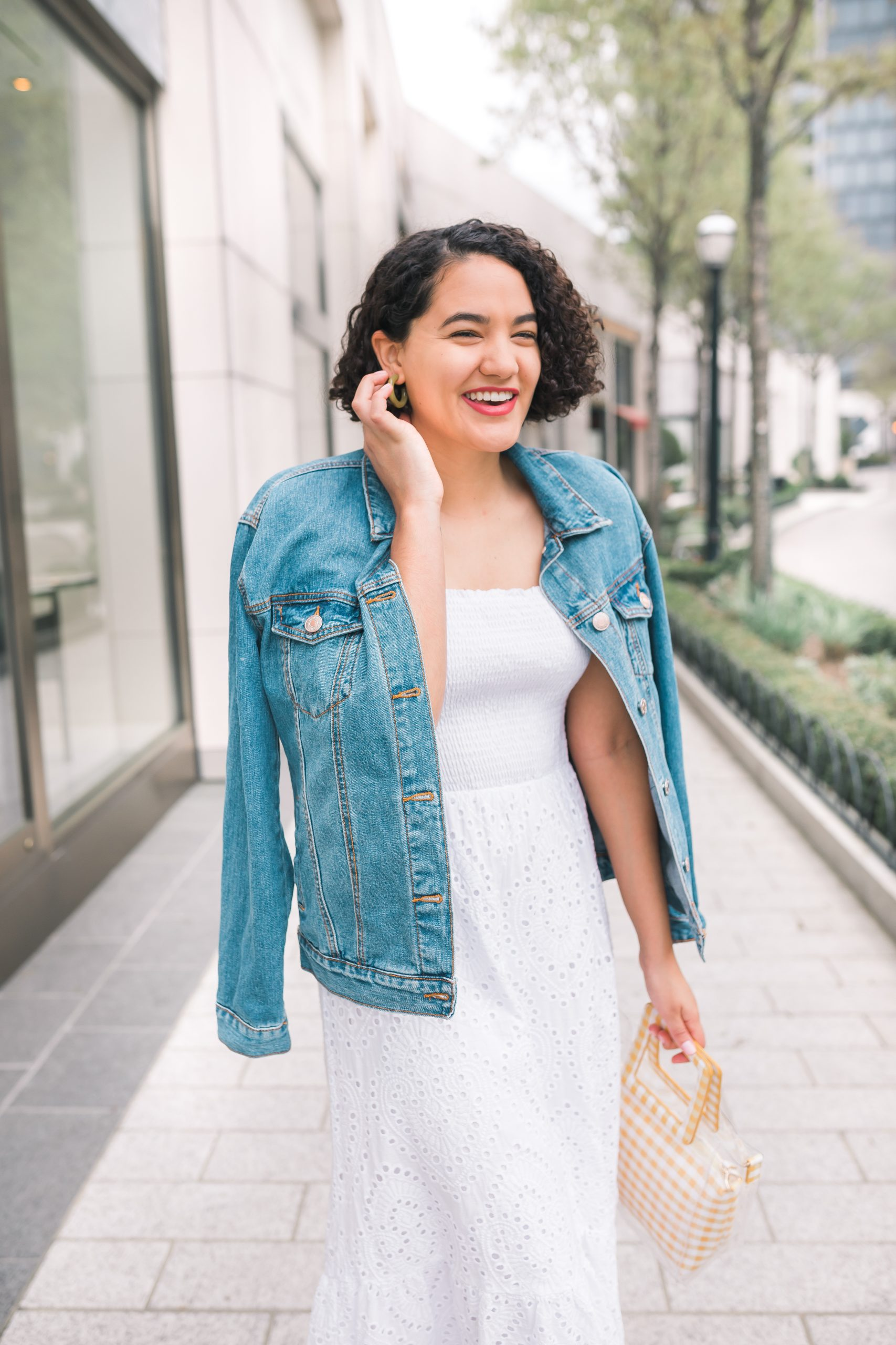 girl wearing a white eyelet midi dress a jean jacket and tan sandals close up