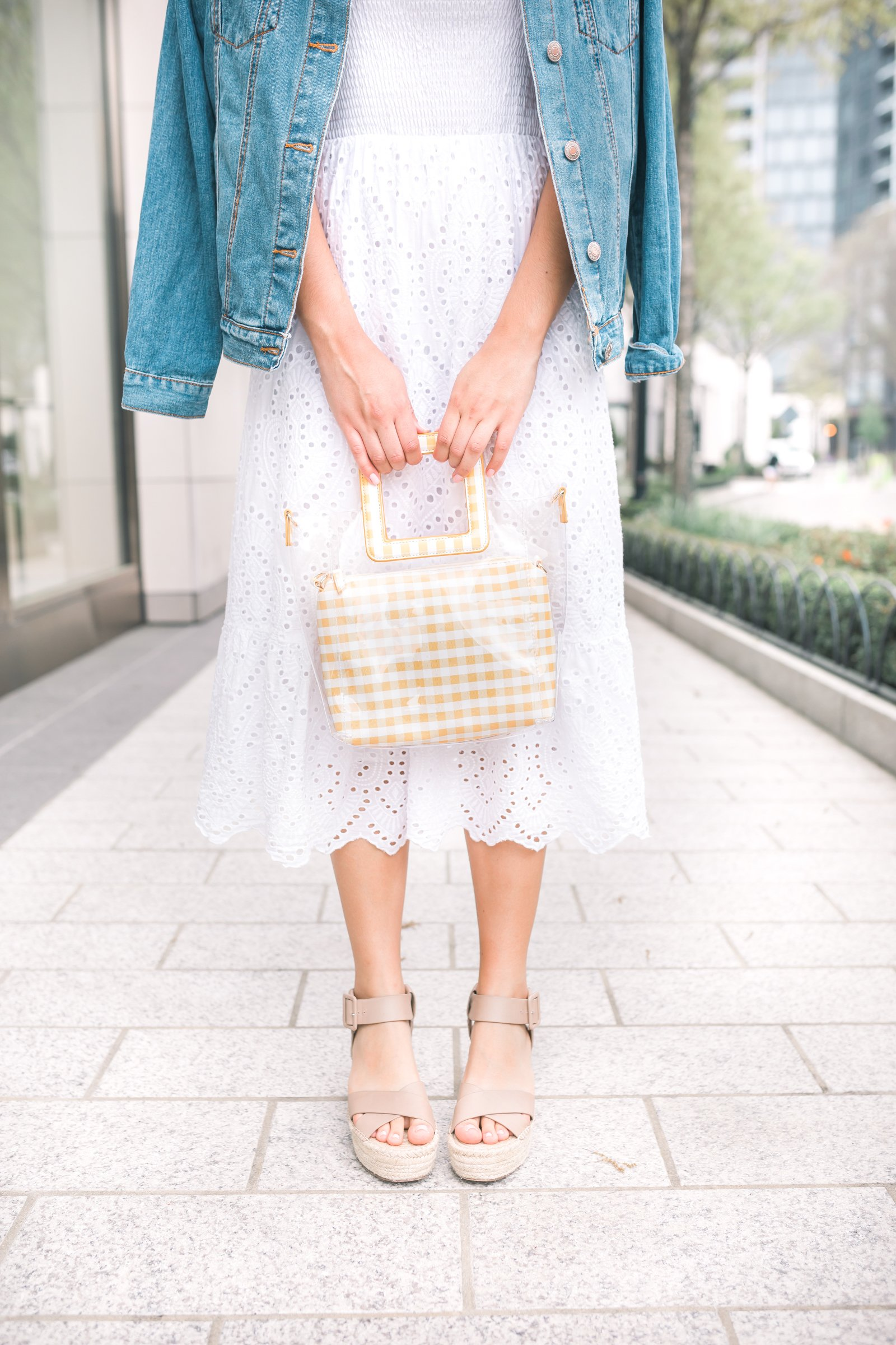 girl wearing a white eyelet midi dress a jean jacket and tan sandals