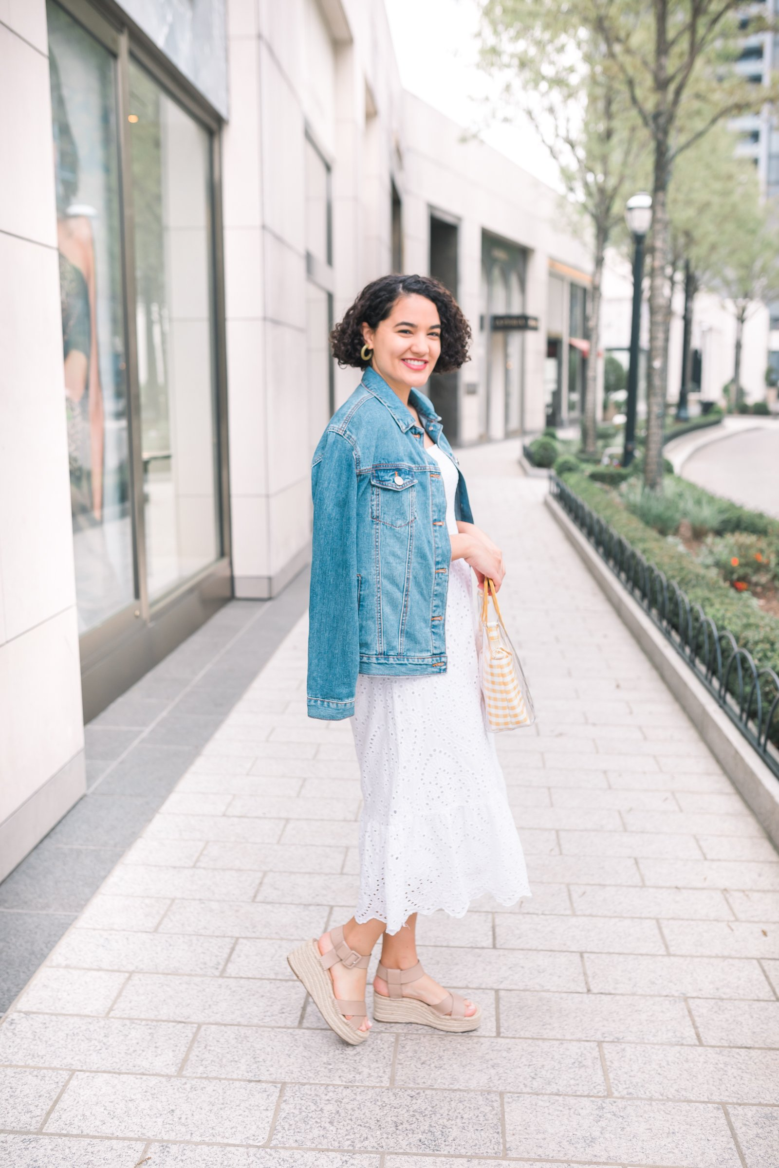 girl wearing a white eyelet midi dress a jean jacket and tan sandals side view