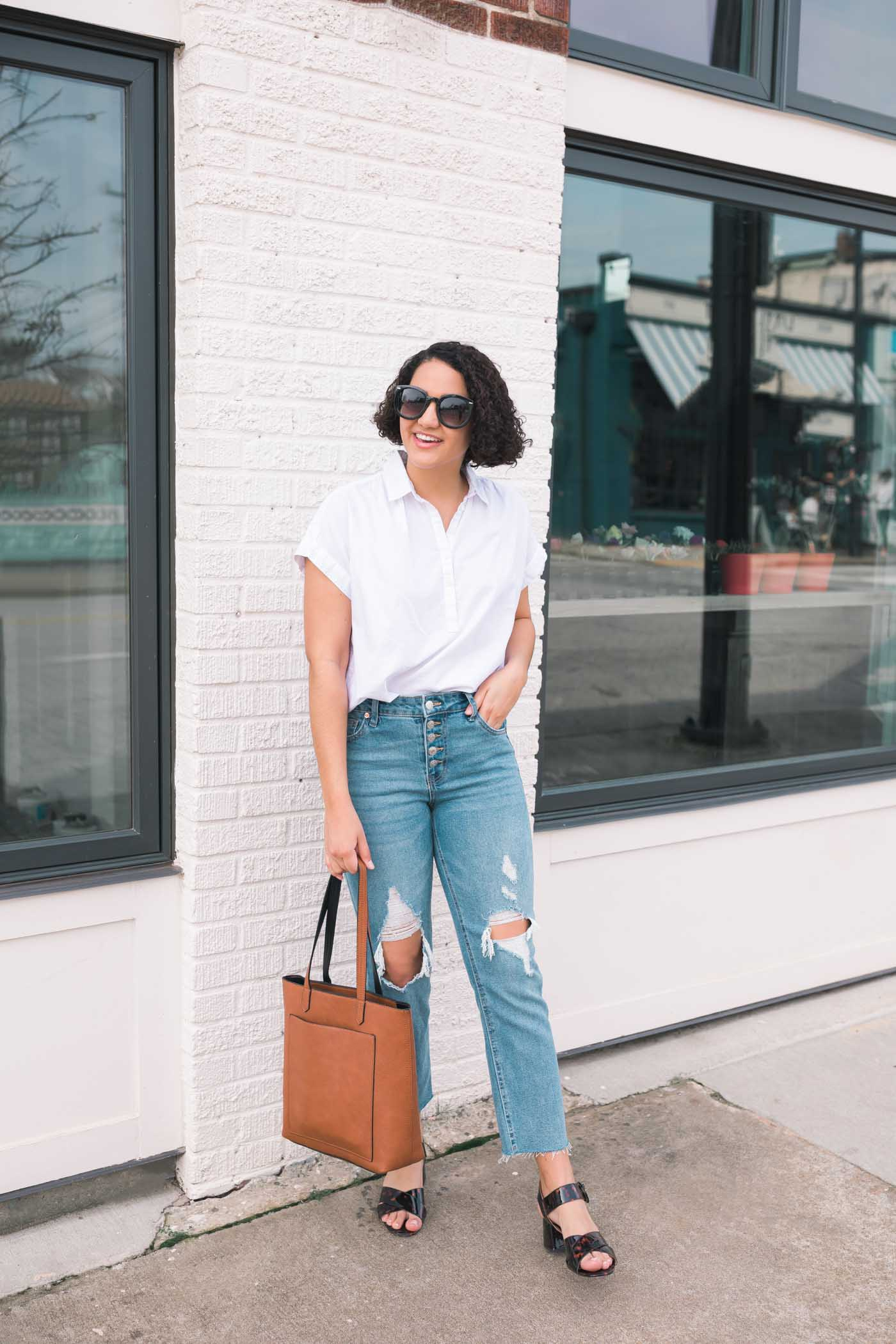 girl with curly hair wearing a white blouse, ripped mom jeans, a cognac tote bag, and sunglasses