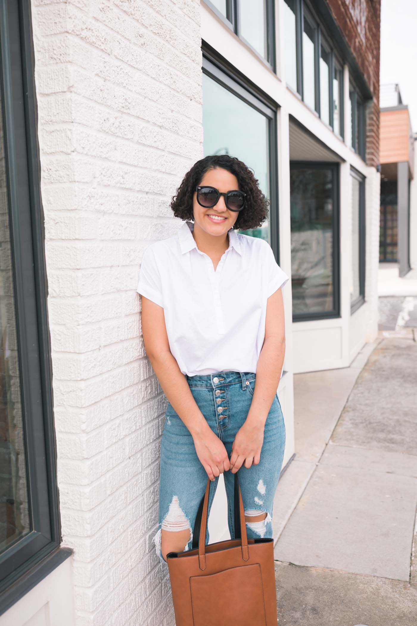 white blouse, ripped mom jeans, cognac tote bag, and sunglasses