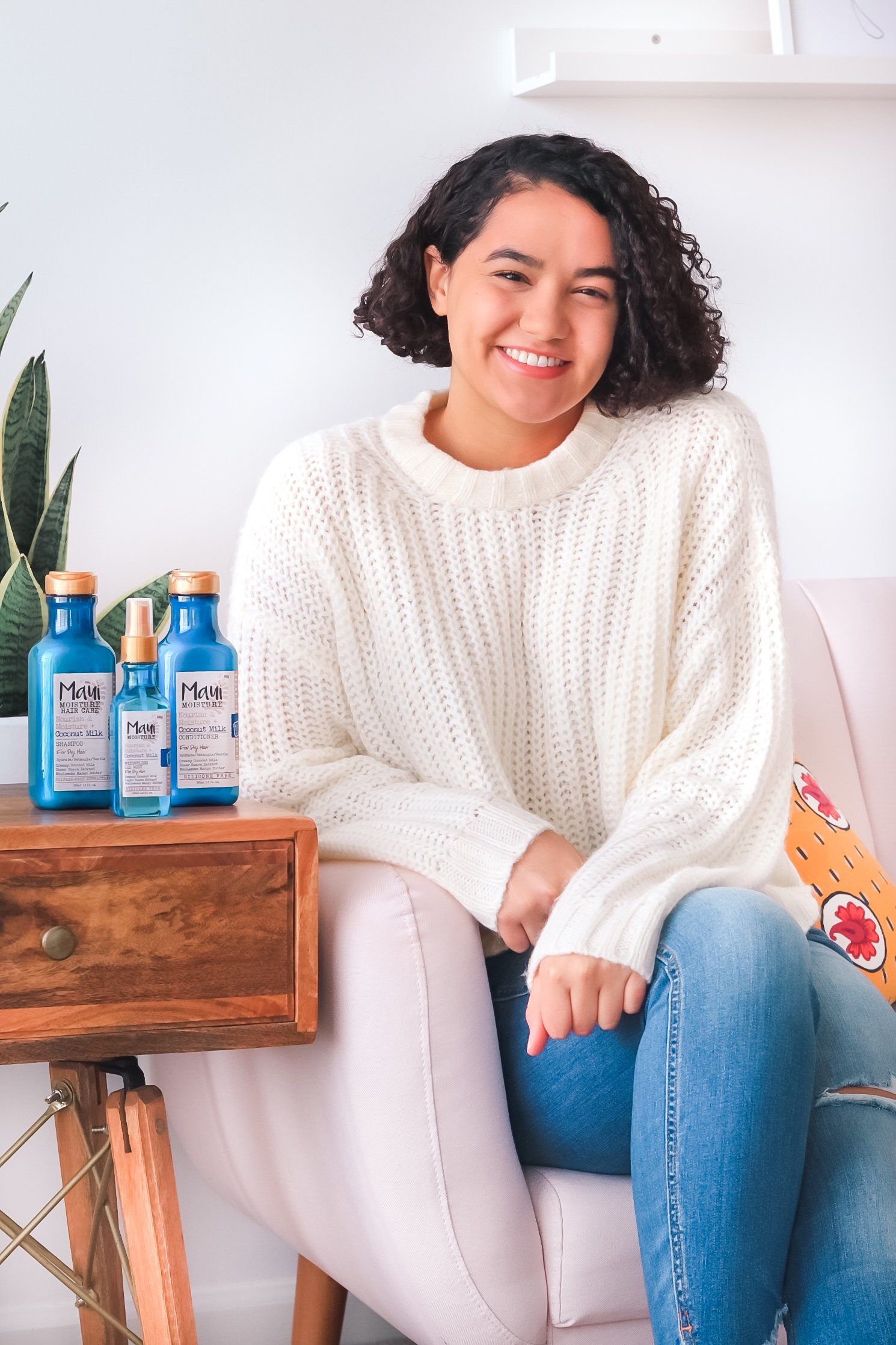 girl sitting on couch with maui moisture products next to her