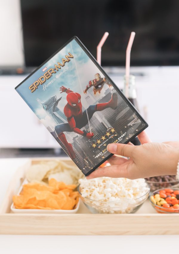 girl holding a spiderman dvd in front of a snack tray