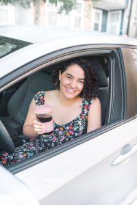 girl sitting in car drinking coffee