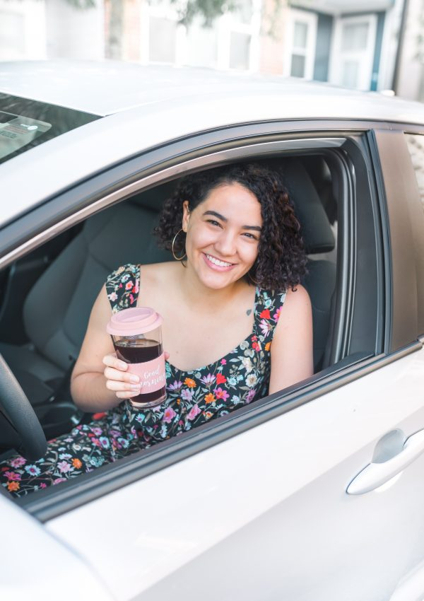 girl sitting in car drinking coffee