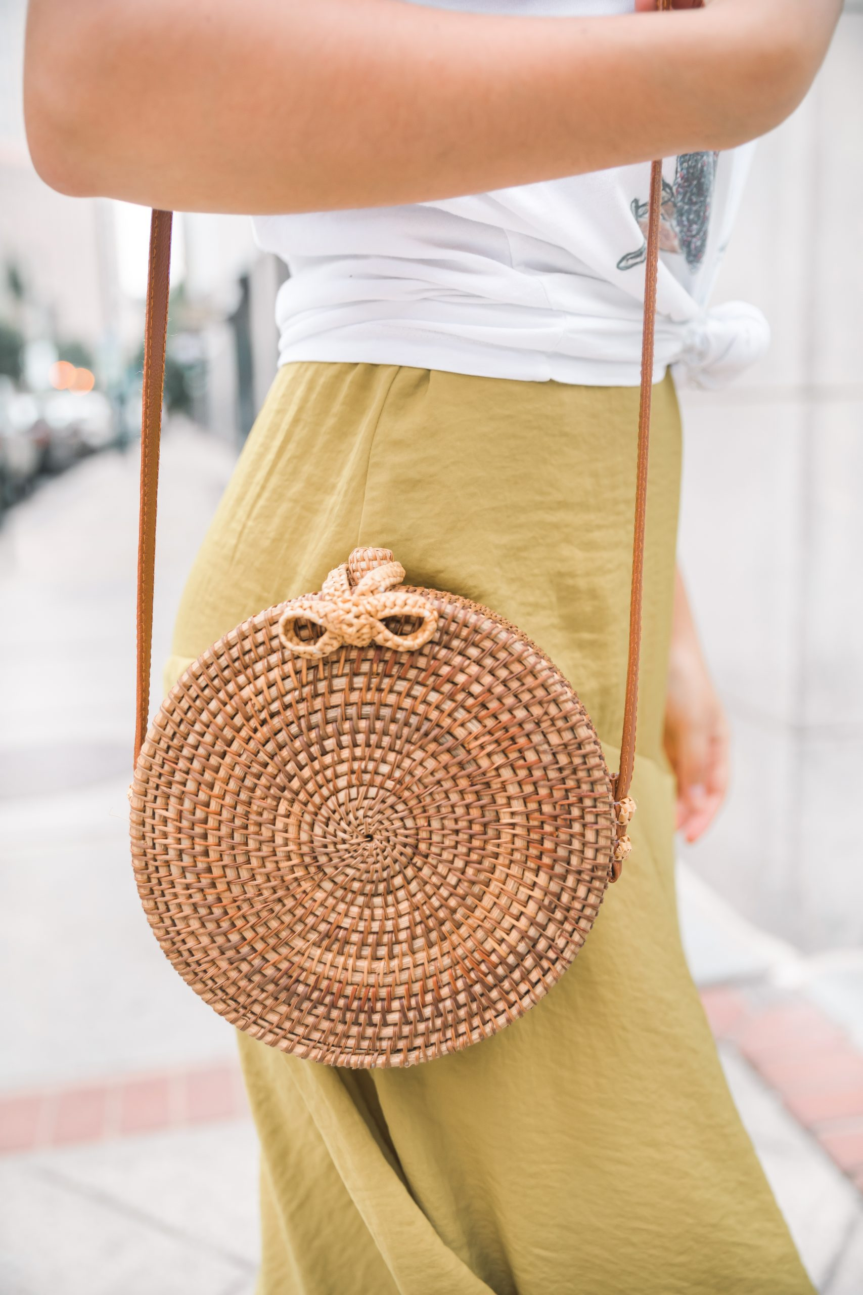 girl holding a round rattan bag