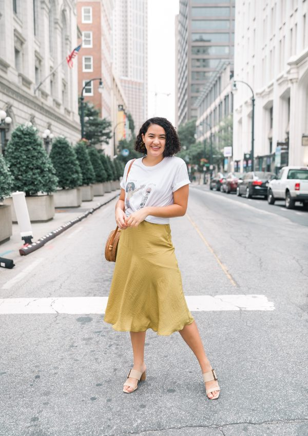 girl standing in city street wearing a graphic tee and yellow midi skirt