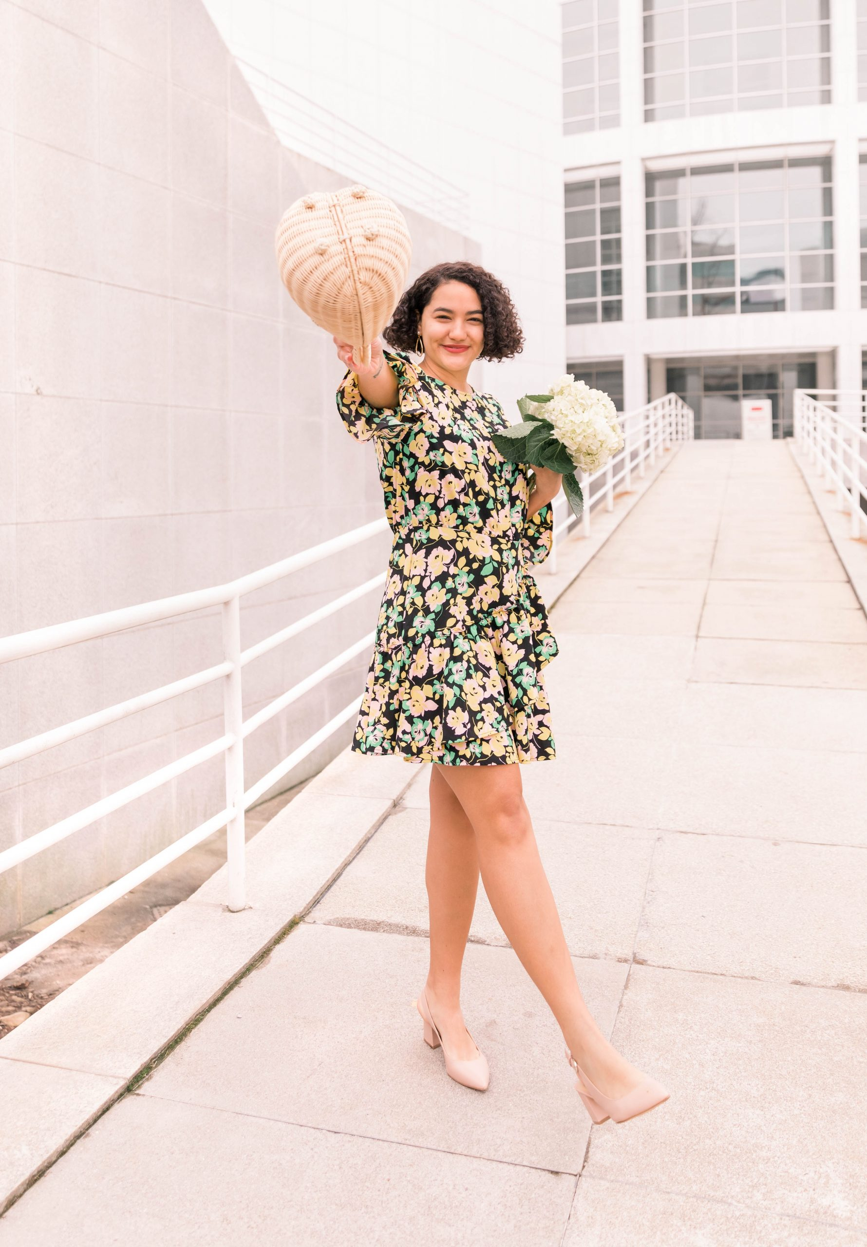 a girl wearing heels and a floral dress who is holding a woven bag and hydrangeas